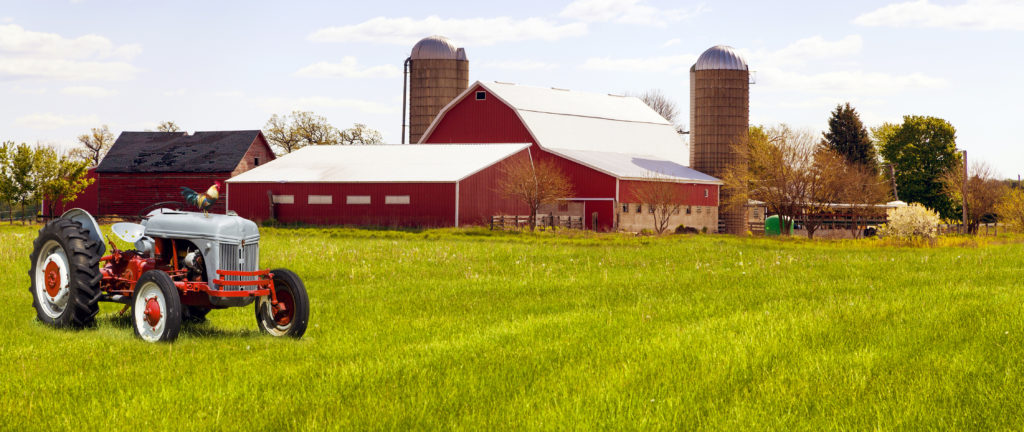 Farm scene with tractor in foreground and barns in background